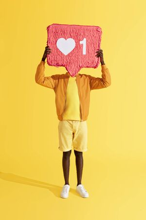 Like. Man holding social media like icon near head on yellow background. Full length portrait of male with heart notification pinata in studio Stock Photo
