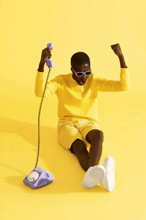 Happy excited man with phone screaming, celebrating on yellow background. Emotional black male model with retro purple telephone in studio