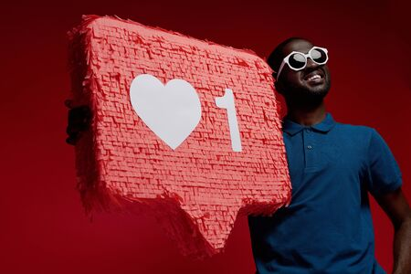 Happy black man with social media like icon pinata on red background. Portrait of smiling male model in sunglasses demonstrating huge heart notification sign 스톡 콘텐츠