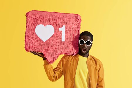 Social media like. Surprised black man with like icon pinata on yellow background. Colorful portrait of shocked male model in sunglasses with huge like sign