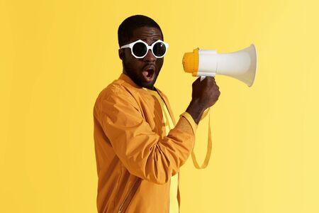 Verrast zwarte man met megafoon op gele achtergrond. Studioportret van geschokt Afrikaans Amerikaans mannelijk model in manierzonnebril met luidspreker