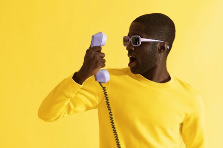 Surprised man in sunglasses with purple phone on yellow background. Portrait of shocked black male model with emotional scared face expression with telephone in studio Stockfoto
