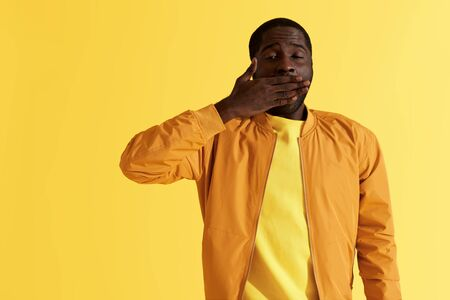Sleepy tired black man yawning on yellow background portrait. Exhausted african american male model closing mouth with hand felling fatigue, studio shot