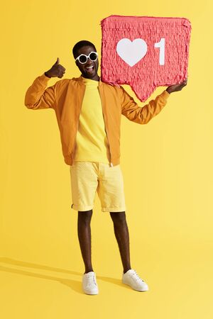 Smiling black man with like icon pinata showing thumbs up on yellow background. Studio shot of happy male model showing like with hand, holding heart button, social media symbol