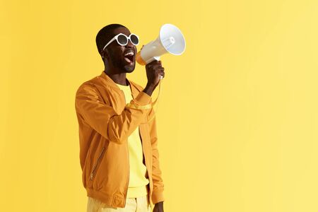 Werbung. Mann schreit Ankündigung im Megaphon auf gelbem Hintergrund. Porträt eines afroamerikanischen männlichen Models in Modekleidung mit Lautsprecher im Studio Standard-Bild