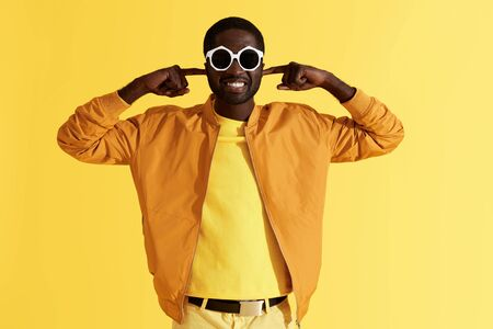 Smiling man in sunglasses closing ears with hands on yellow background. Portrait of black male model sticking  fingers in ears, ignoring annoying loud noise, studio shot 版權商用圖片