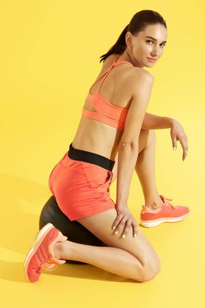 Fitness woman in sports wear relaxing on med ball on colorful yellow background. Full lenght portrait of sexy girl model with fit body in fashion sportswear in studio