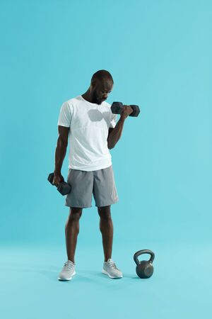 Exercise. Sports man doing dumbbell biceps workout on colorful background. Fitness male model in stylish active wear exercising, doing dumbbell curl