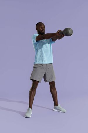 Workout. Man doing kettlebell swing exercise, sports training on purple background. Fitness male model exercising with kettle bell at studio Stock Photo