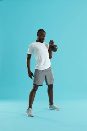 Workout. Sports man doing kettlebell exercise training on blue background. Full length portrait of fitness male model doing kettle bell clean and press exercising