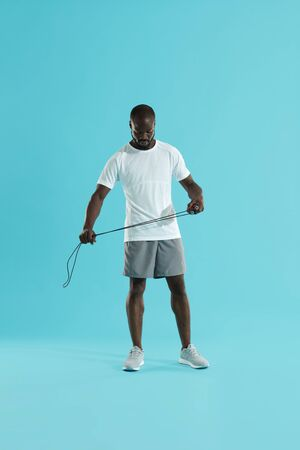 Sports man in sportswear with skipping rope at studio. Full length shot of african american male fitness model with jumping rope on colorful blue background