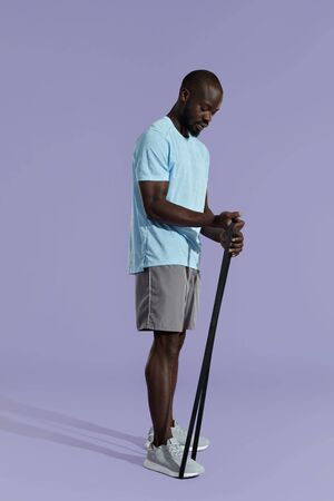 Workout. Sports man doing training band exercise on purple background. Full length portrait of black male model in stylish active wear exercising with resistance band at studio Standard-Bild