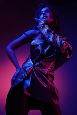 Women style. Fashion model in stylish dress in colorful neon lights at studio portrait. Fashionable girl in glamorous clothes in pink and purple ultraviolet colors at night club