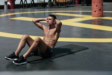 Sport man doing abs crunches exercise, fitness workout at street. Male athlete exercising on yoga mat, doing abdomen muscle training outdoors at gym Stock Photo