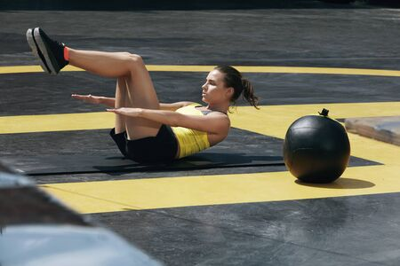 Sport woman doing abs exercise workout at outdoor gym. Fitness girl model exercising on yoga mat, doing abdomen muscle training at health club