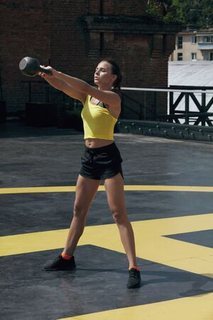 Workout. Sport woman doing kettbell swing exercise outdoors. Fitness girl in sports clothes exercising, doing kettle bell exercises at street