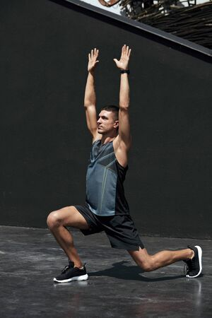 Sport man stretching body, doing stretch exercise on street. Male athlete with fit body warming up before workout outdoors Banco de Imagens