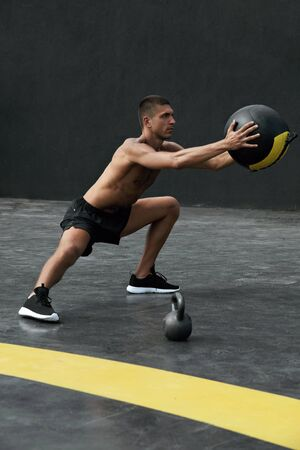 Sport man doing side lunge exercise with med ball at fitness gym. Male athlete with fit body stretching legs, doing body workout outdoors at street Banco de Imagens
