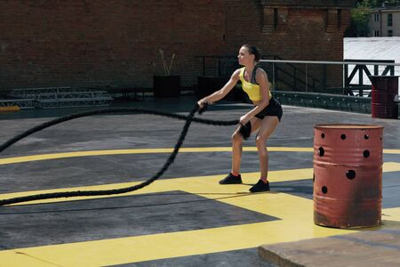 Sport woman doing battle ropes exercise workout at gym. Athletic girl exercising, doing functional fitness training with heavy ropes outdoors at street