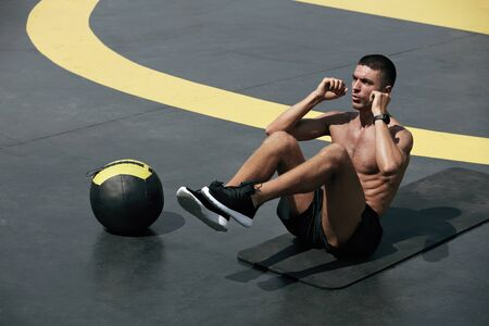 Fitness workout. Man doing abs sitting crunch exercise at street. Male athlete exercising on yoga mat, doing abdomen muscle crunch training at outdoor gym