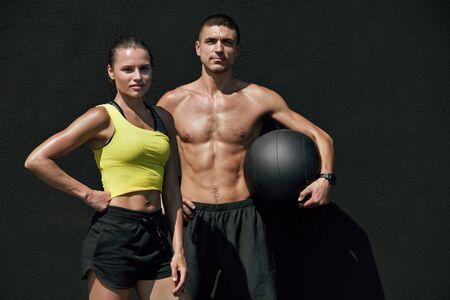 Gente de fitness en ropa deportiva después del entrenamiento con med ball al aire libre. Feliz pareja sonriente en forma después de un ejercicio exitoso sobre fondo gris Foto de archivo