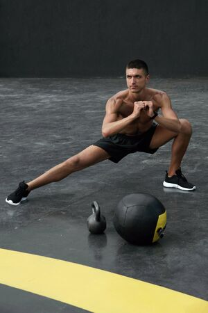 Sport man stretching legs, doing side lunge exercise at gym. Male athlete with fit body warming up, doing leg stretch workout outdoors at street Banco de Imagens