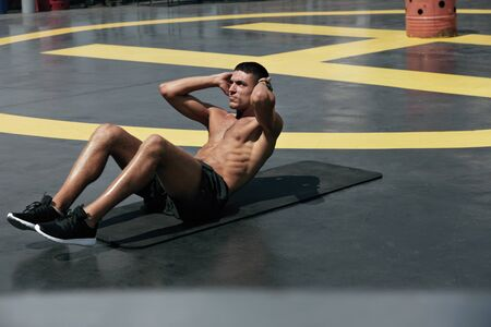 Sport man doing abs crunches exercise, fitness workout at street. Male athlete exercising on yoga mat, doing abdomen muscle training outdoors at gym Stok Fotoğraf
