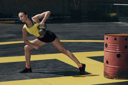 Sport woman doing back exercise workout with weights outdoors. Fitness girl in sports clothes exercising, doing kettlebell row on street