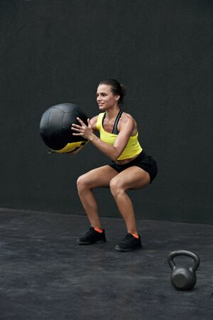 Workout. Fitness woman doing squat exercise with med ball at gym. Sport female model in sportswear and fit body squatting, exercising outdoors on street