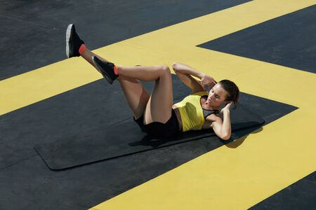 Sports woman doing bicycle crunch workout at gym. Fitness girl doing abs crunches exercise on yoga mat outdoors at street on roof Stock Photo