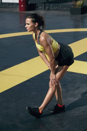 Fitness woman in sportswear stretching legs before workout outdoors. Full length portrait of fit girl in sport clothes warming up at street