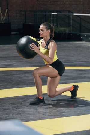 Exercise. Sport woman doing leg workout with med ball outdoors. Fitness girl with fit body exercising, doing lunge training with medicine ball on street Stock Photo