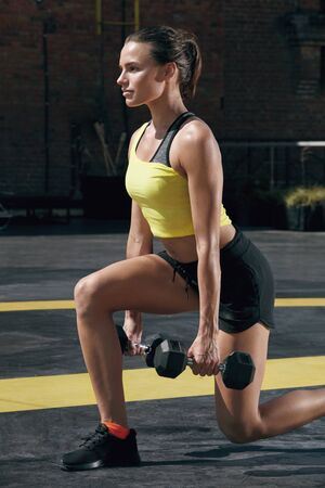Workout. Fitness woman doing leg exercise with dumbbell at street gym. Girl athlete with fit body in sport clothes exercising, doing lunge training outdoors