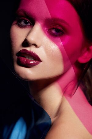 Beauty face makeup. Fashion portrait of girl model with lipstick under color. Closeup of glamorous girl with sexy dark red lips make-up and glowing skin under pink and blue colors. High quality