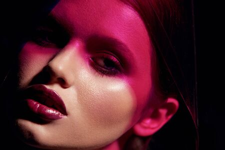 Makeup beauty. Woman model with dark lipstick under pink light. Closeup portrait of glamorous girl with beautiful sexy make-up, lip gloss and glowing skin under color lights. High quality image