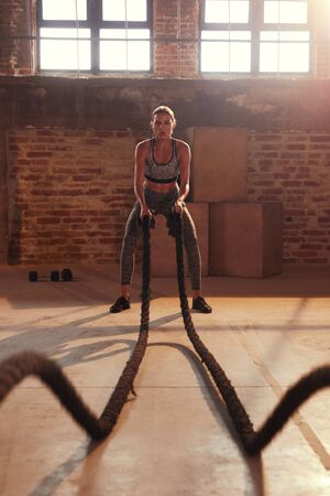 Fitness workout. Sport woman doing battle rope exercise at gym. Girl athlete with fit body exercising, doing functional training with heavy ropes indoors Reklamní fotografie