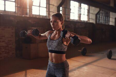 Donna sportiva che fa esercizio di fitness con manubri in palestra. Archivio Fotografico