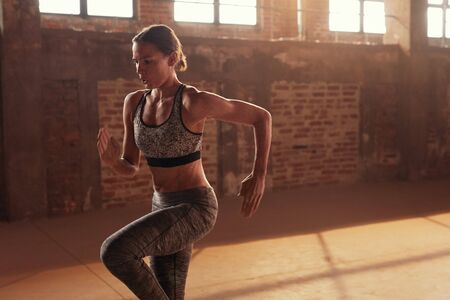 Fitness workout. Woman running on spot, doing cardio exercise at gym. Portrait of girl with fit body in stylish sport wear doing fat burning functional training indoors