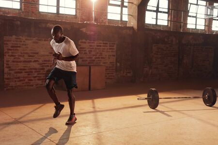 Fitness workout. Fit man running on spot, doing cardio exercise at gym. Portrait of male athlete with fit body doing fat burning training indoors Archivio Fotografico