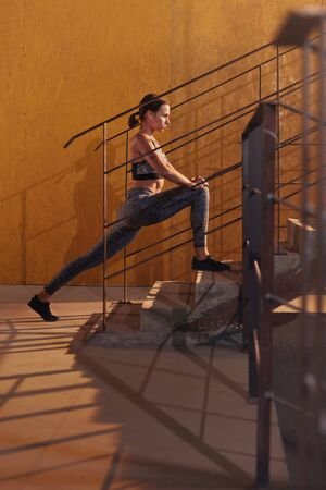 Fitness woman stretching legs on stairs before workout. Beautiful girl athlete with fit body in sport clothes warming up, doing leg stretch exercise before training or running
