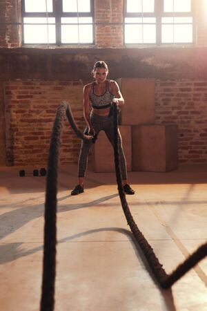 Rope workout. Sport woman doing battle ropes exercise at gym. Fitness girl athlete with fit body exercising, doing functional training with heavy ropes indoors
