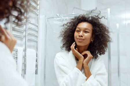 Eye skin care. Woman with beauty patch mask on skin under eyes at bathroom portrait. Beautiful african american girl model with afro hair and natural makeup using eye patches, collagen pads at home Standard-Bild