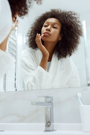 Lips skin care. Woman applying lip balm looking in mirror at bathroom. Portrait of beautiful african girl model with beauty face and natural makeup applying lip product with finger 版權商用圖片 - 131003309