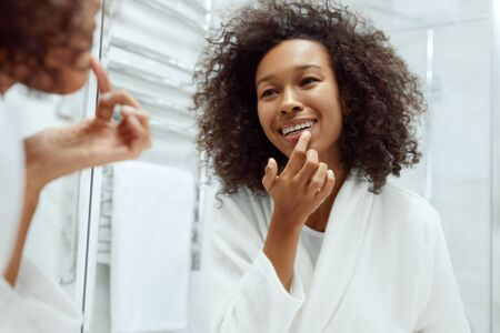 Lips skin care. Woman applying lip balm looking in mirror at bathroom. Portrait of beautiful african girl model with beauty face and natural makeup applying lip product with finger 版權商用圖片