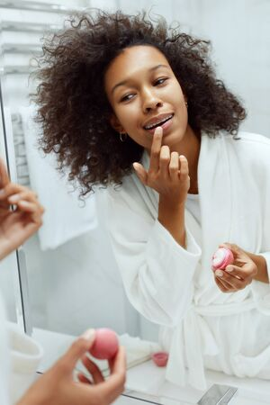 Lips skin care. Woman applying lip balm looking in mirror at bathroom. Portrait of beautiful african girl model with beauty face and natural makeup applying lip product with finger