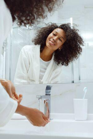 快乐的女人在盥洗室里看着镜子洗手。美丽快乐的非洲女孩的肖像与非洲式发型通过早晨美容例行