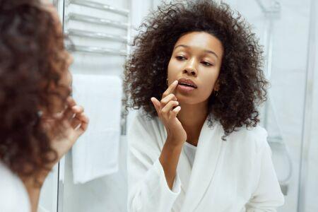 Cuidado de la piel de los labios. Mujer aplicar bálsamo labial mirando en el espejo en el baño. Retrato de hermosa niña africana modelo con rostro de belleza y maquillaje natural aplicando producto labial con el dedo