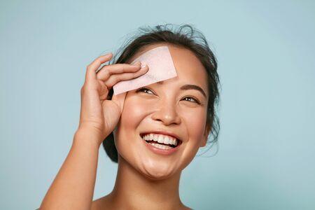 Face skin care. Smiling woman using oil blotting paper portrait