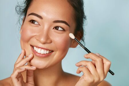Beauty. Woman applying makeup on eyes with cosmetic brush