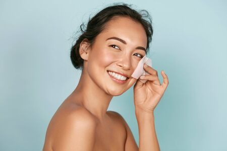 Face skin care. Smiling woman using oil blotting paper portrait